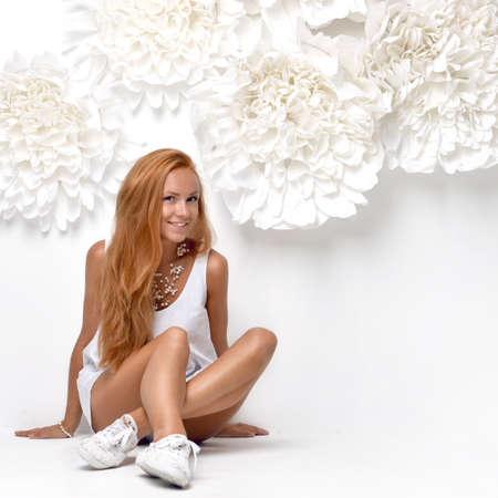 sensual girl: Beautiful fashion redhead woman sitting neat wall with big flowers on a white background Stock Photo