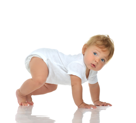child girl nude: Infant child baby girl in diaper crawling happy looking at the corner trying to stand up isolated on a white background Stock Photo