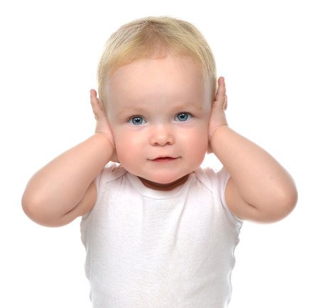 hands over ears: infant child baby toddler sitting closed her hands over ears and hears nothing isolated on a white background Stock Photo