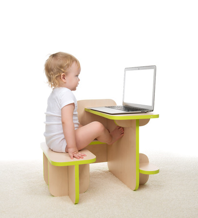 infant hand: Infant child baby girl toddler sitting with hands typing on modern wireless computer laptop keyboard isolated on a white background