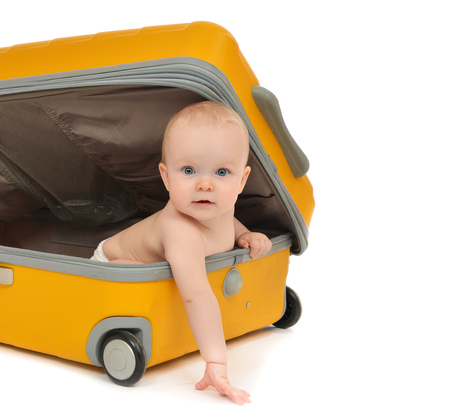 suitcases: Happy infant baby toddler sitting in yellow plastic travel suitcase on wheels getting ready for vacation isolated on a white background