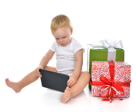 happy christmas: Infant child baby toddler kid with tablet pc device ordering presents gifts isolated on a white background Christmas new year concept. Stock Photo