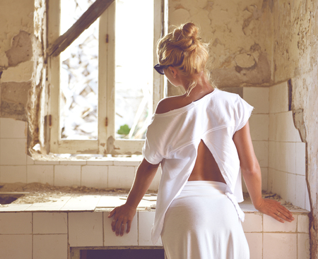 Young woman thinking of remodeling old house kitchen standing at countertop backward with broken tiles window sink