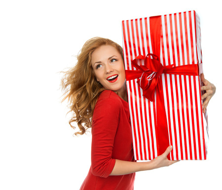 looking in corner: Happy young woman hold red Christmas wrapped gift present smiling and looking at the corner isolated on a white background