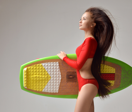hold: Beautiful brunette young woman with long hair in red bikini and surfboard over a gray background