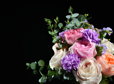 Beautiful bouquet of bright white pink purple roses flowers with green leafs on black background