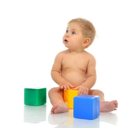baby playing toy: Infant child baby boy toddler playing holding green blue yellow bricks in hands on a floor on and looking up isolated a white background Stock Photo