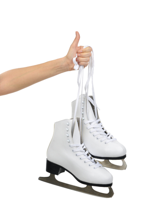 Hand with thumb up sign holding woman ice skates isolated on a white background