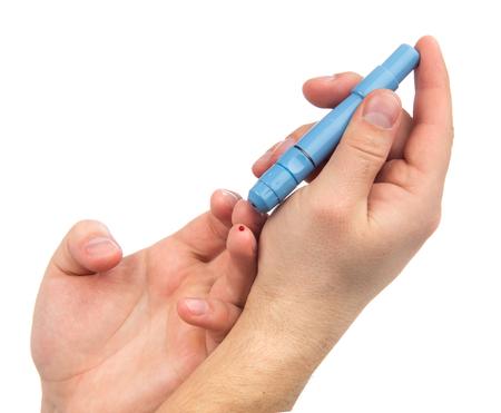 diabetes: Lanceta de la diabetes en la mano pinchazo dedo para hacer punciones para obtener pequeñas muestras de sangre para la prueba de nivel de glucosa en sangre con glucómetro aislado en un fondo blanco Foto de archivo