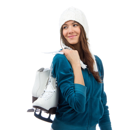 looking in corner: Young woman holding ice skates for winter ice skating sport activity in white hat smiling looking at the corner  isolated on a white background Stock Photo