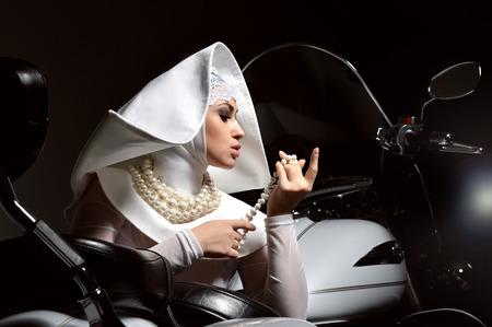 Portrait of high fashion glamor portrait of beautiful stylish Caucasian young woman model in sister of Mercy nun cloth near morcycle bike Stock Photo
