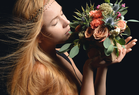 Beautiful red hair woman sniff vintage rustic bouquet of wild roses Carnation flowers with green leafs of eucalyptus and thistle in box windy hair on black background Standard-Bild