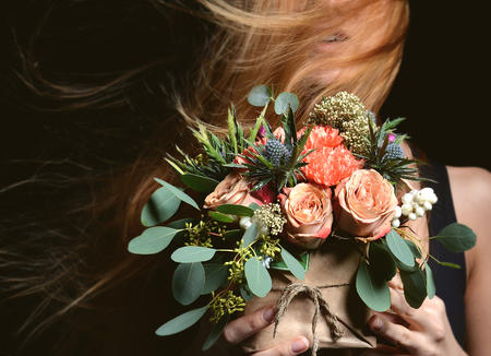 Beautiful red hair woman with vintage rustic bouquet of wild roses Carnation flowers with green leafs of eucalyptus and thistle in box windy hair on black background Standard-Bild
