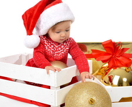 holding a christmas ornament: Christmas baby child in santa hat holding gold ball decoration near present gift box. New Year 2016 holiday concept isolated on a white background Stock Photo