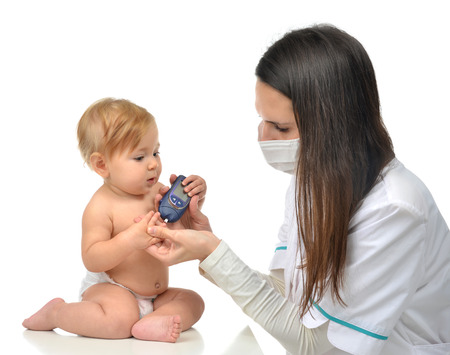blood glucose level: Doctor measuring glucose level blood chemistry test from diabetes child baby using glucometer and small drop of blood from finger and test strips isolated on a white background