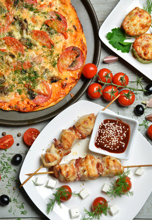 rustic food: Tasty food composition italian pizza kebab bbq tomatoes olives garlic on wooden rustic table background.