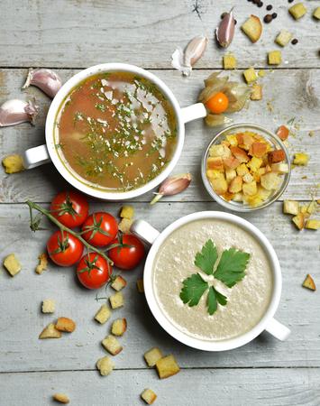 ajo: Dos cuencos de sopa vegetariana composición de setas y pescado sopa de crema en un tazón con ajo eneldo perejil y migas de pan en el fondo de madera rústica Foto de archivo