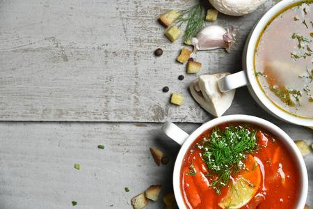 ajo: Cuencos de sopa de pescado composici�n con crema de espacio de la copia de texto sopa de champi��n y tomate en un taz�n con ajo eneldo perejil y migas de pan en el fondo de madera r�stica Foto de archivo