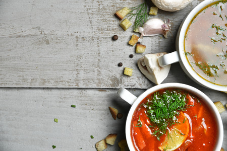 hot soup: Soup bowls composition with text copy space mushroom cream soup fish and tomato in bowl with garlic parsley dill and croutons on rustic wood background