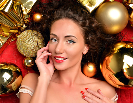happy christmas: Close up portrait of happy young woman in winter christmas decoration ornament smiling with gold balls new year background