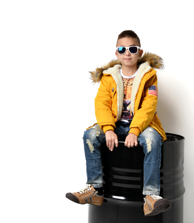 white winter: Fashion beautiful little boy in yellow winter clothing jacket jeans and sunglasses sitting over white background