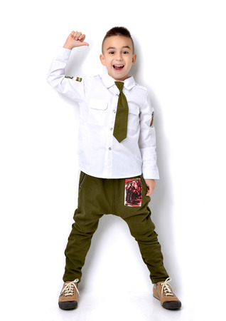 millitary: Fashion beautiful little boy in millitary t-shirt green jeans standing and giving thumbs up sign over white background Stock Photo
