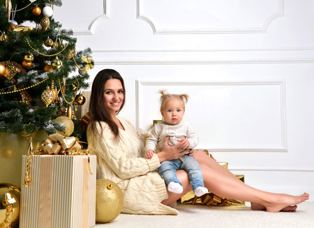 young tree: Christmas Family with mother woman with baby Kid girl and gold christmas tree with present gifts. Happy young Parent and Child at Home Celebrating New Year. Christmas scene