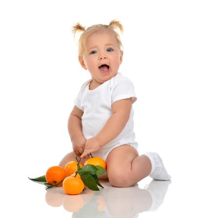 bebe sentado: niña niño del niño que se sienta feliz sonriendo gritando con mandarina fresca mirando a la cámara aislada en un fondo blanco. Navidad concepto de año nuevo