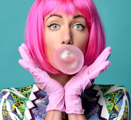 Close up funny fashion portrait of cheerful woman inflating the bubble gumin hot pink party wig on a mint background.