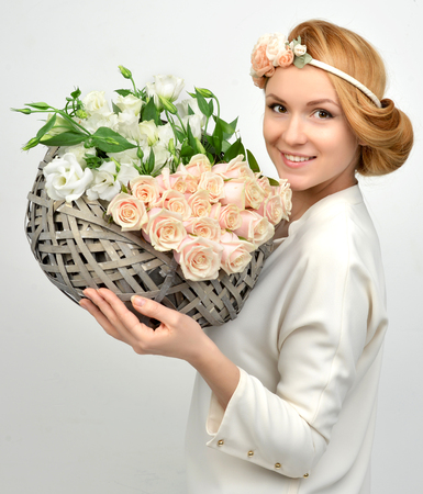 Beautiful woman with pastel color bouquet of wild white roses flowers in pretty vintage rustic box smiling