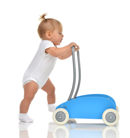 Cute smiling baby girl toddler with toy walker make first steps isolated on a white background Stockfoto