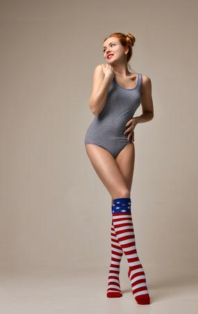 Sexy young beautiful full body woman posing in black modern bikini underwear on a warm grey background
