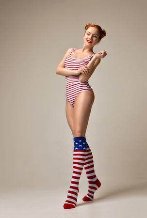 Sexy jonge mooie full body vrouw poseren in zwarte moderne bikini ondergoed op een warme grijze achtergrond