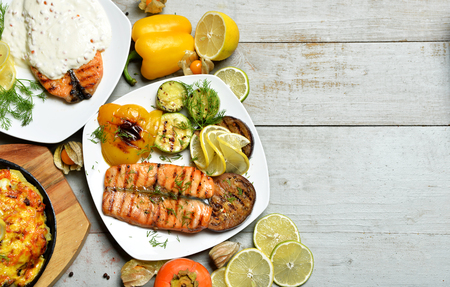 zander: Grilled salmon Fish steak Fillet with BBQ Vegetables meat pie and sauce on vintage rustic wood background
