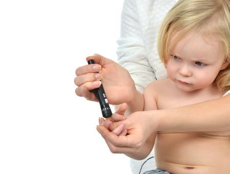 医者は白い背景の分離レベルの血液検査を測定ブドウ糖の糖尿病赤ちゃん幼児の指を刺す 写真素材
