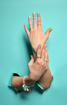 Beautiful woman hands with yellow pink white pattern nail polish and silver stacking rings and bracelets on a mint background
