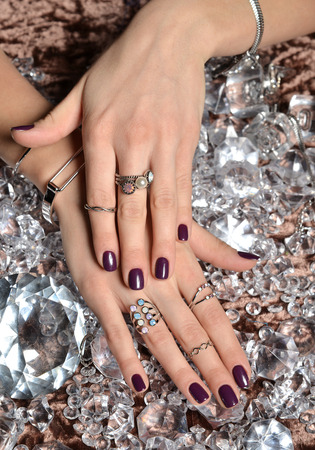diamond background: Beautiful woman hands with purple pattern polish nails and silver stacking rings and bracelets on a ice diamonds background Stock Photo