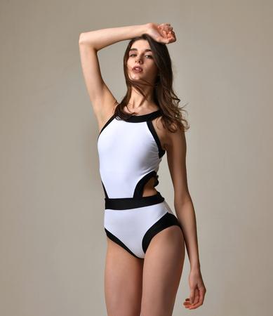 jungen unterwäsche: Sexy junge schöne Frau in schwarz und weiß moderne Unterwäscheweste an einem warmen grauen Hintergrund aufwirft Lizenzfreie Bilder