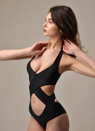 completo: Mujer hermosa joven atractiva que presenta en la ropa interior del chaleco moderno negro mirando a la esquina en un fondo gris cálido