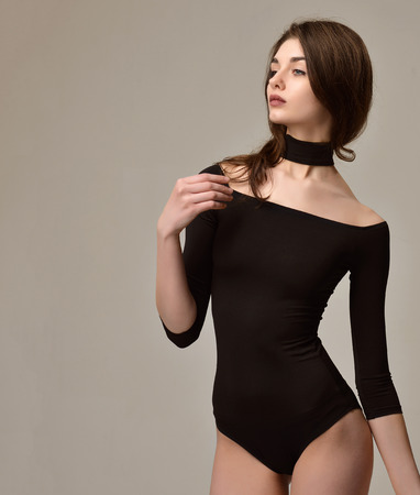 Sexy young beautiful woman posing in black modern bikini underwear vest on a warm grey background