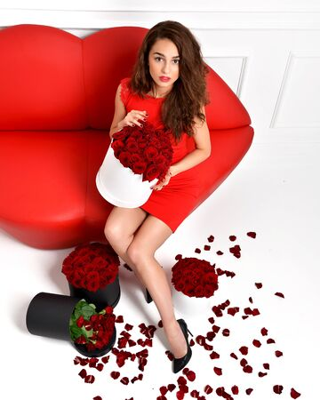 love sexy: Beautiful luxury fashionable woman legs in high hills and red dress with roses bouquet and petals
