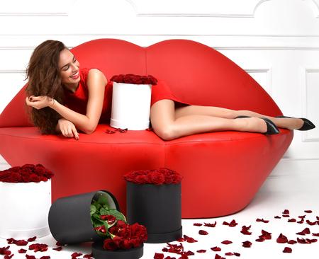 mujer con rosas: Mujer de moda hermosa lujo mentira en los labios rojos sofá cama y vestido rojo con rosas ramo de flores y pétalos de risa Foto de archivo