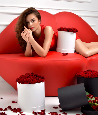 Beautiful Luxury Fashionable Woman Lying On Red Lips Sofa Couch And Red  Dress With Roses Bouquet