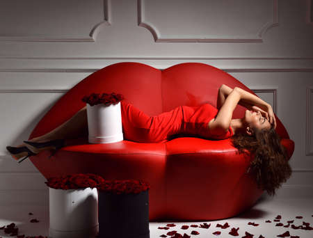 bunch of red roses: Beautiful luxury fashionable woman lying on red lips sofa couch and red dress smiling lughing with roses bouquet, petals Stock Photo