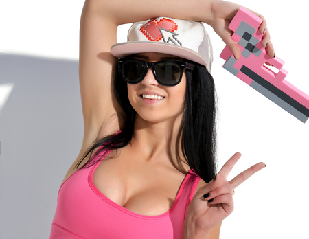 woman with gun: Sexy Brunette Woman in cap with pink pixels gun toy and sunglasses on a white background Stock Photo