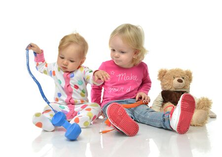 girl  care: Kids play at home. Children playing with phones Little girl having fun with her sister Siblingsnear toy bear. Toddler preschooler and baby at day care.