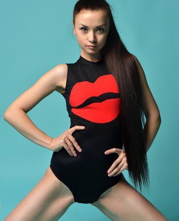 femme brune sexy: Bonne jeune belle femme brune posant en maillot de bain rouge bikini moderne avec des lèvres rouges menthe fond bleu