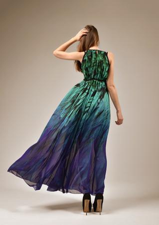 Vista posteriore del caucasica corpo pieno di bella donna in abito lungo ventoso e alte colline