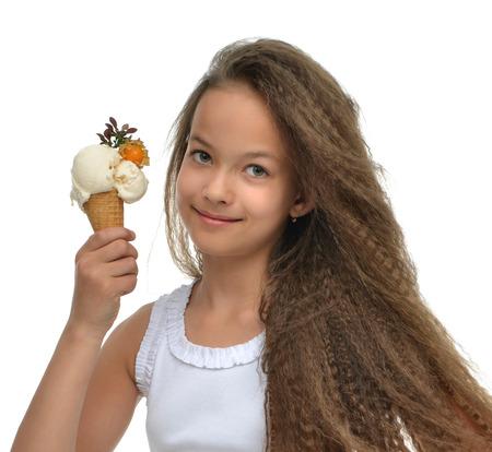 白い背景で隔離コーナーを見て笑みを浮かべてワッフル コーン バニラ アイスクリームを保持しているかわいい女の子子供
