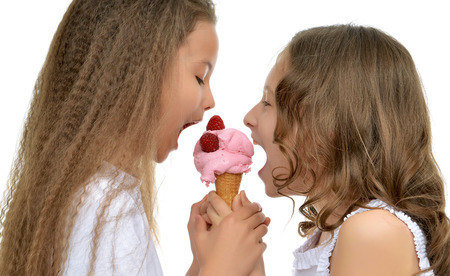 Young baby girls happy ready for eating red raspberry ice cream in waffles cone smiling yelling isolated on a white background Banco de Imagens